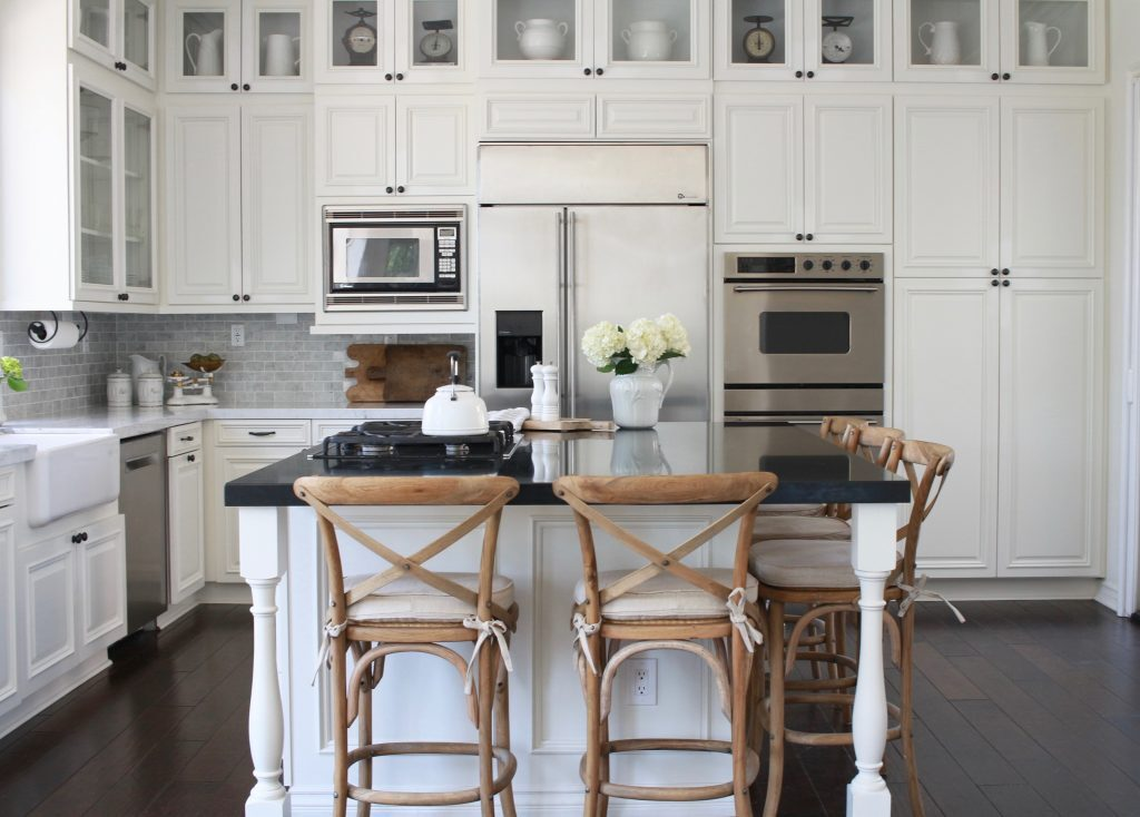 Maison De Cinq's kitchen remodel, this kitchen shows White Dove in a neutral light. The gray undertones are present, brought out by the natural light and the gray backsplash. The dark marble island is made all the more dramatic against the White Dove cabinets.