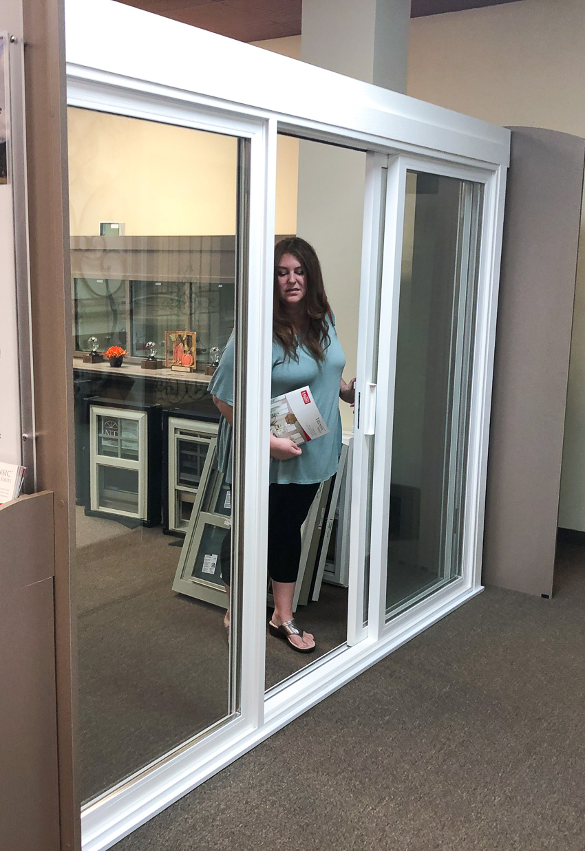 Woman closing Trinsic Series patio door at Milgard store