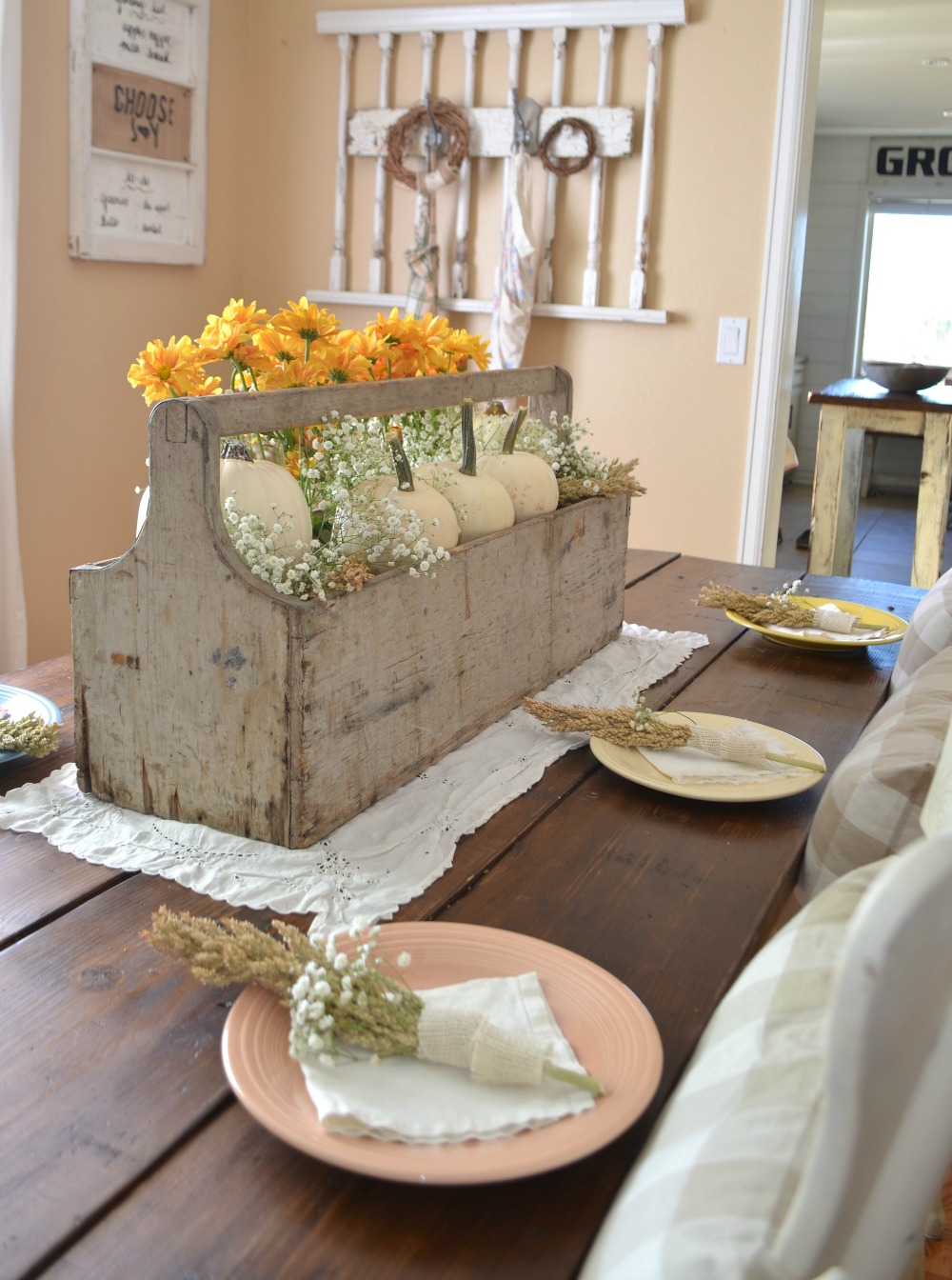 Thanksgiving table decor ideas - a large centerpiece filled with mini pumpkins and flowers!
