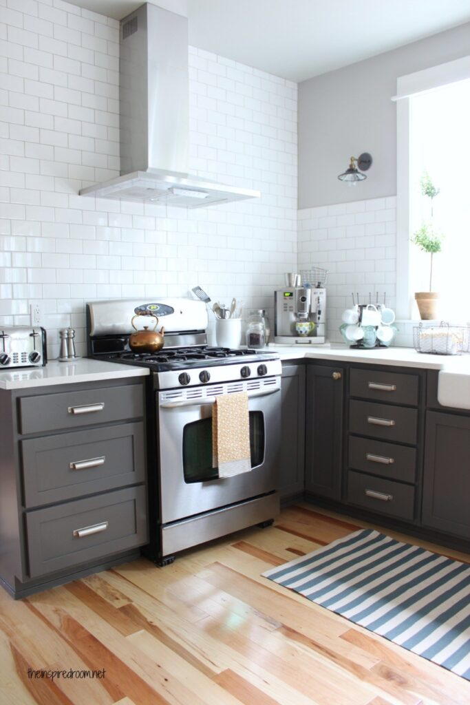 Kendall Charcoal kitchen cabinets with white subway tile, nickel hardware and Caesarstone white countertops.