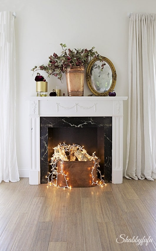 classic fake fireplace with string lights covering birch logs