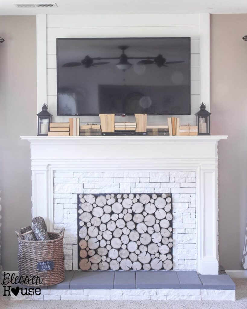 white DIY fireplace with stacked log insert